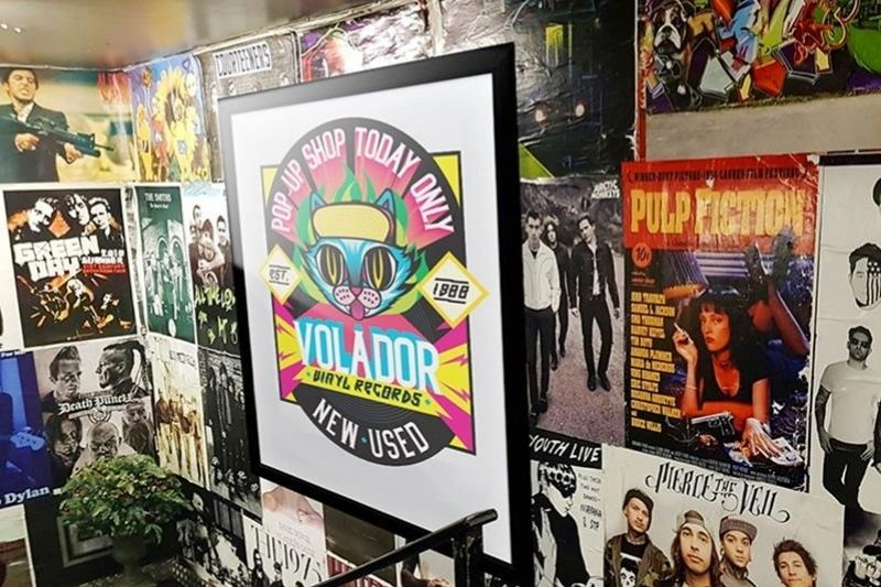 Printed poster in a frame hanging in a music shop with a background of album cover posters