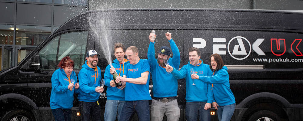 The Peak UK team celebrate their win with champagne