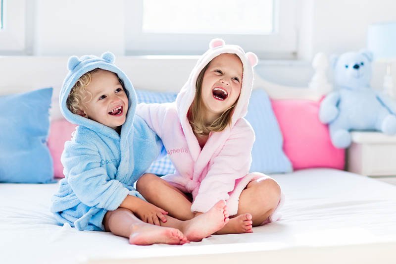 two children wearing personalised bath robes