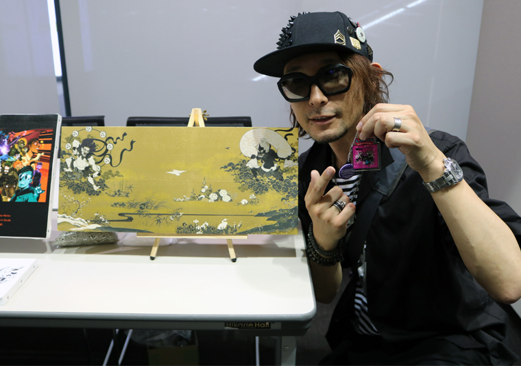 LIMITS Digital Art Battle - Baron Ueda (Japan) holding a one-of-a-kind creation he designed and standing in front of artwork he produced using a Roland VersaUV digital printer