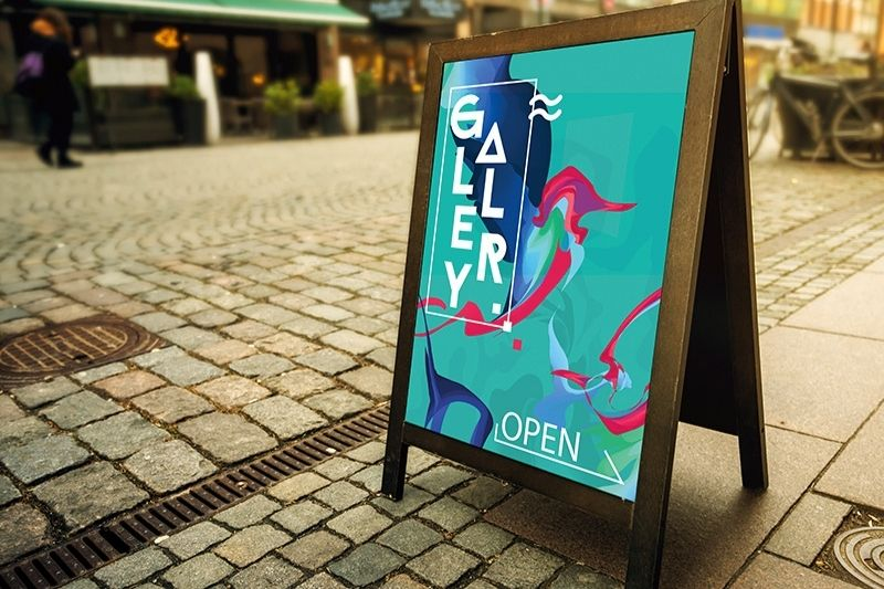 Gallery open poster on an A-frame sign on pavement in a street