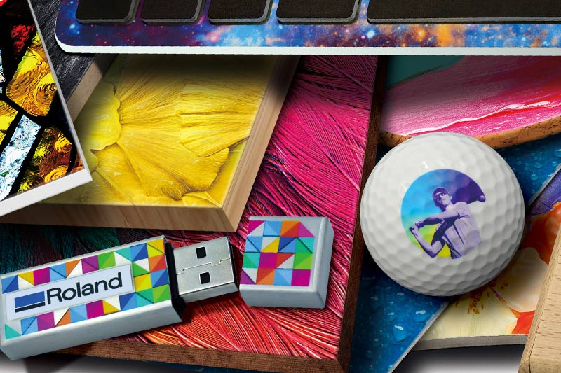USB stick branded with corporate Roland logo, golf ball and other items printed on a UV printer