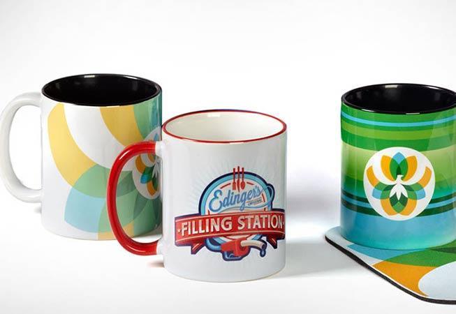 Three branded mugs with corporate logos and company designs