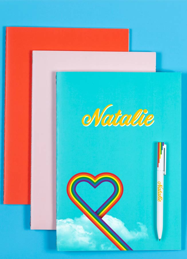 Three notebooks in red, pink and blue with rainbow heart and name printed on the front and personalised pen accessory